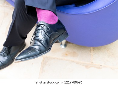 A wedding guest shows black moccasins and pink stockings.