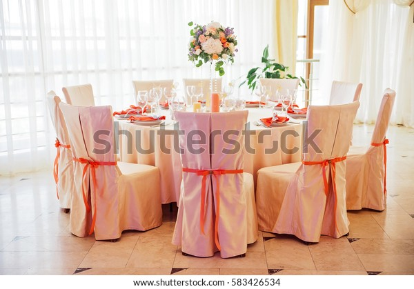 Wedding guest table decorated with bouquet and chairs with bows