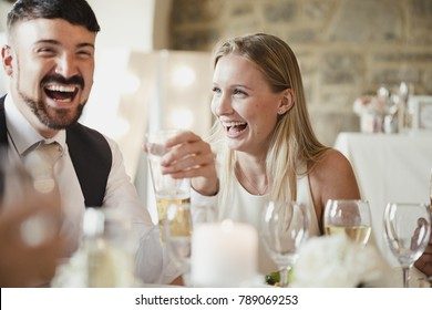 Wedding guests are enjoying themselves while sitting at the table for the meal. They are talking and laughing while drinking wine and lager.
