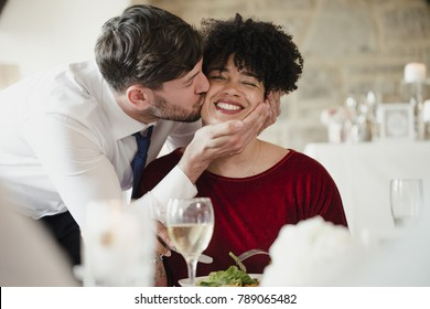 Wedding guests having fun at the meal. A woman with an afro is getting a big kiss on the cheek by the groom on his wedding day.