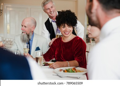 Wedding guests are socialising while enjoying the starter of their meal.