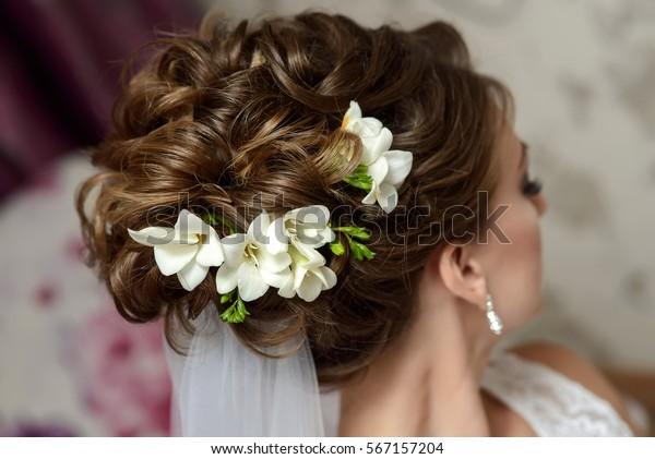 Hochzeitshaare stylen. Braunhaarige Braut mit lockiger Frisur mit Barrette. Hochzeitskonzept