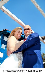 Wedding. Happy couple day wedding. Beautiful bride and groom cuddled. Cheerful married couple standing and smiling. Wedding couple staying beside the blue white house.
