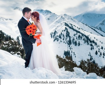 Wedding happy snowboarders couple just married at mountain. Husband wearng a jacket, shirt, butterfly, trousers. Bride dressed in white dress. Wedding ceremony at alps mountains at winter
