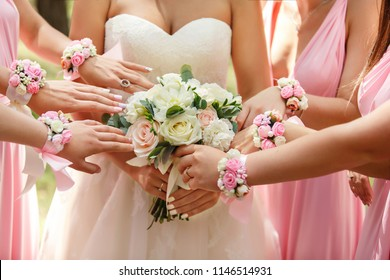 Wedding help. Bride holding wedding bouquet, bridesmaids pulling hands to him at wedding day. Happy marriage and wedding party concept