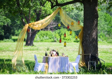 Wedding inspiration. Set the table in nature, decorated with hanging lamps