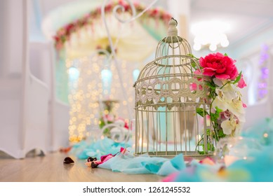 Wedding interior. Scenery during the holiday. Design elements at a wedding. An empty cage for a bird