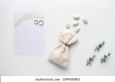 Wedding invitation card, candy, rings and oregano branches. Top view.