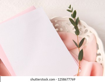 Wedding invitation mockup with blush silk, eucalyptus and white pottery