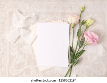 Wedding invitation mockup with white ribbons and flowers in blush colors