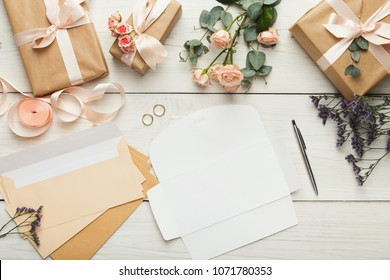Wedding invitations and craft envelopes on white wooden background. Top view on paper cards, rings and pink roses bouquet, copy space. Memmorable date organization concept