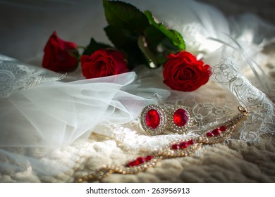 Wedding jewelry for the bride: veil, ear rings, bracelet and red roses