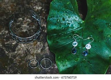 Wedding jewelry set of bride: earrings, two rings and silver bracelet on wooden background