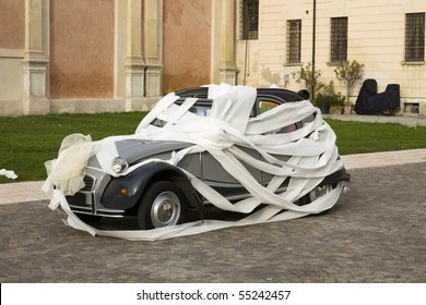 Wedding joke with a car wrapped by toilet-paper