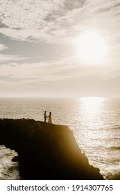 wedding just maried couple on the rocks sunset standing together enjoying the ocean sea view