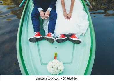 wedding legs in red gym shoes on a boat