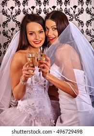 Wedding lesbians dyke girl in bridal dress drinking champagne on home wallpaper background.