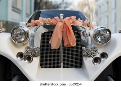 The wedding limousine decorated by tapes and colors expects the groom and the bride for walk