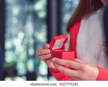 wedding, love, engagement and happiness concept - smiling woman in white dress holding red gift box with diamond ring over beige background