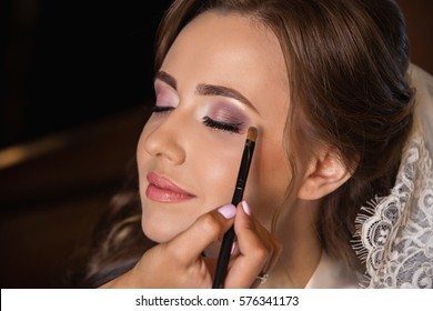 Wedding make up for beautiful bride with pure skin. Makeup artist makes makes make-up with brush in hand.