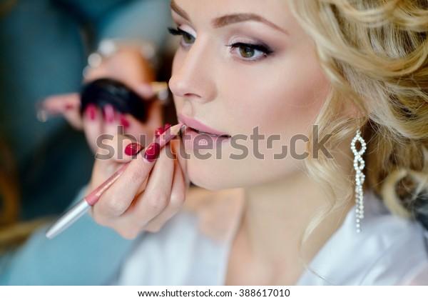 Hochzeitsschminker, der Braut nachmacht. Schönes sexy Model Mädchen drinnen. Schöne Frau mit lockigem Haar. Frauenporträt. Großer Morgen einer süßen Dame. Nahaufnahme von Händen nahe der Seite