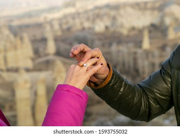 wedding, marriage proposal in Cappadocia, Nevsehir Turkey. Man gives wedding ring to his lover, fiance, girlfriend. Fairy tale chimneys  with blue sky on background. Love Valley in Capadocia