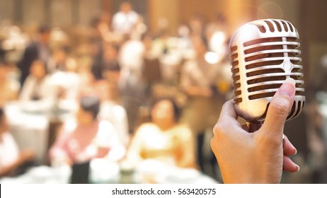 Wedding meeting and event on stage concept - Close up retro microphone in singer hand on stage of business meeting or event whit flare light effect and copyspace