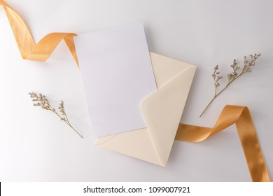 A wedding mock up concept. Wedding Invitation, envelopes, cards Papers on white background with ribbon and decoration. Top view, flat lay, copy space