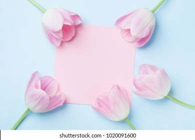 Wedding mockup with pink paper list and tulip flowers on blue table top view. Beautiful floral pattern. Flat lay style.