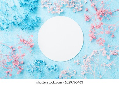 Wedding mockup with white paper list and flowers on blue pastel table top view. Beautiful floral pattern. Flat lay style. Spring Woman day card.