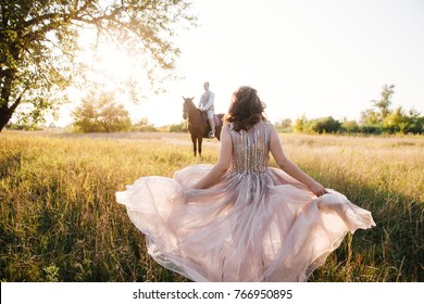 Wedding near the river in field at sunset. Groom on brown horse. Bride in light airy dress in color of dusty rose. Beige dress with sparkles. Light suit with bow tie. bride and groom embrace and kiss.