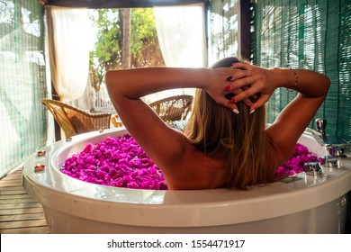 wedding night.beautiful bride and handsome groom relaxing in bath tropical flowers at luxury hotel resort.man and woman kissing and hugging romantic fruits, candles and champagne.sex in the water.