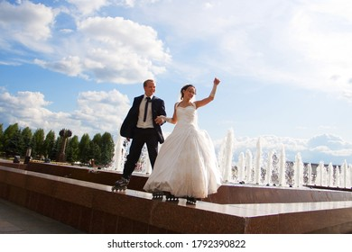Wedding on roller skates. The bride and groom are standing in front of the fountain wearing roller skates. They are happily smiling. Sky is bright and blue. Just merried