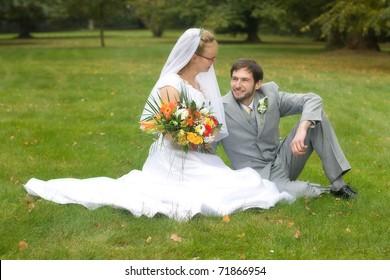 Wedding pair sitting on the lawn