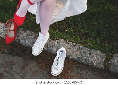 wedding pairs of shoes. Red shoes. White running shoes. the bride puts on sneakers. the bride takes off her shoes