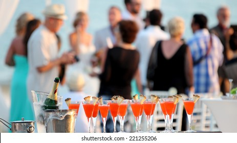 Wedding Party. Red cocktails in glasses and cold champagne ready for party people. Cold chilled champagne in ice bucket and glasses of red cocktail at outdoor wedding reception.