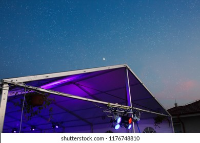 The wedding party tent at night, festival music tent with dj lights, view from the bottom looking clear blue sky with stars and moon at the background