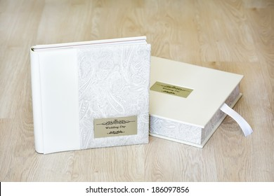 """Wedding photo album and box for it with combined ivory leather cover and metal shield with title """"Wedding day"""" on wooden background."""