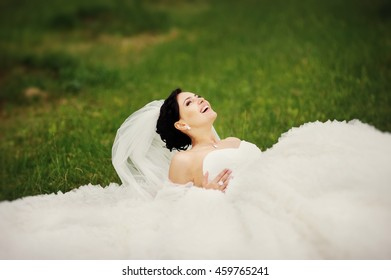 Wedding Photo Beautiful young brunette bride wearing white dress laying on grass in garden