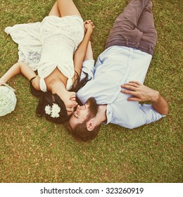 """wedding photo of couple on a grass. """"Instagram"""" style filter applied"""