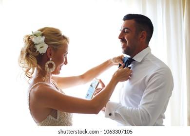 Wedding photo shoot of the newlyweds wedding couple in a beautiful hotel posing near window