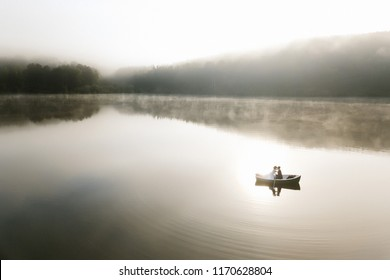 Wedding photo. Shooting with the drone boat love story on a summer morning over forest lake in the fog
