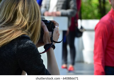 Wedding photographer in the process of his work. Professional photographer shoots a wedding ceremony. A young girl looks into the camera's viewfinder
