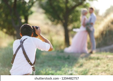 wedding photographer takes pictures of bride and groom in nature. wedding couple on photo shoot. photographer in action