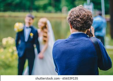 Ein Hochzeitsfotograf fotografiert Braut und Bräutigam in der Natur, der Fotograf in Aktion