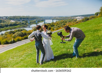 Wedding photographer taking pictures of the bride and groom on a hillside