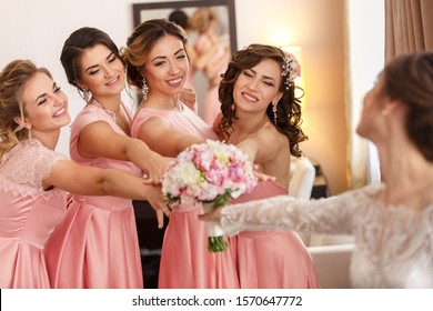 Wedding photography. Bride gives her wedding bouquet to the bridesmaids after wedding ceremony