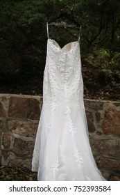 Wedding Photography: Lace Wedding Dress Hanging from an Evergreen Bush outside in front of a Stone Wall