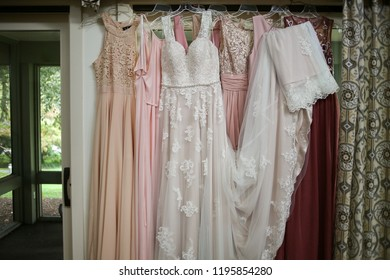 Wedding Photography Mismatched Pink Bridesmaid Dresses Hanging in front of French Doors