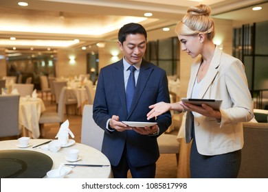 Wedding planner and banquet manager discussing tableware